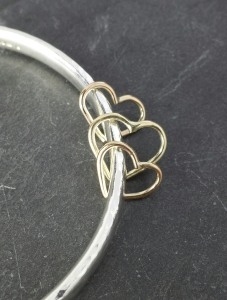 contained on a solid sterling bangle