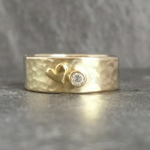 ...medium width hammered 9ct band set with Diana's original solitaire from her engagement ring & an 18ct heart...